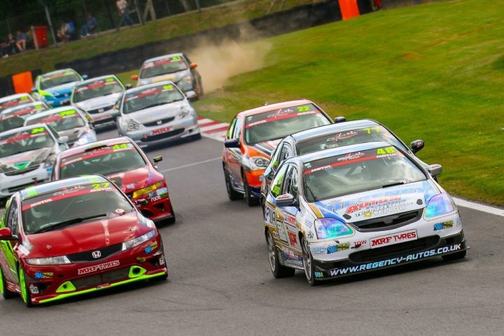 Touring cars racing on track at castle combe