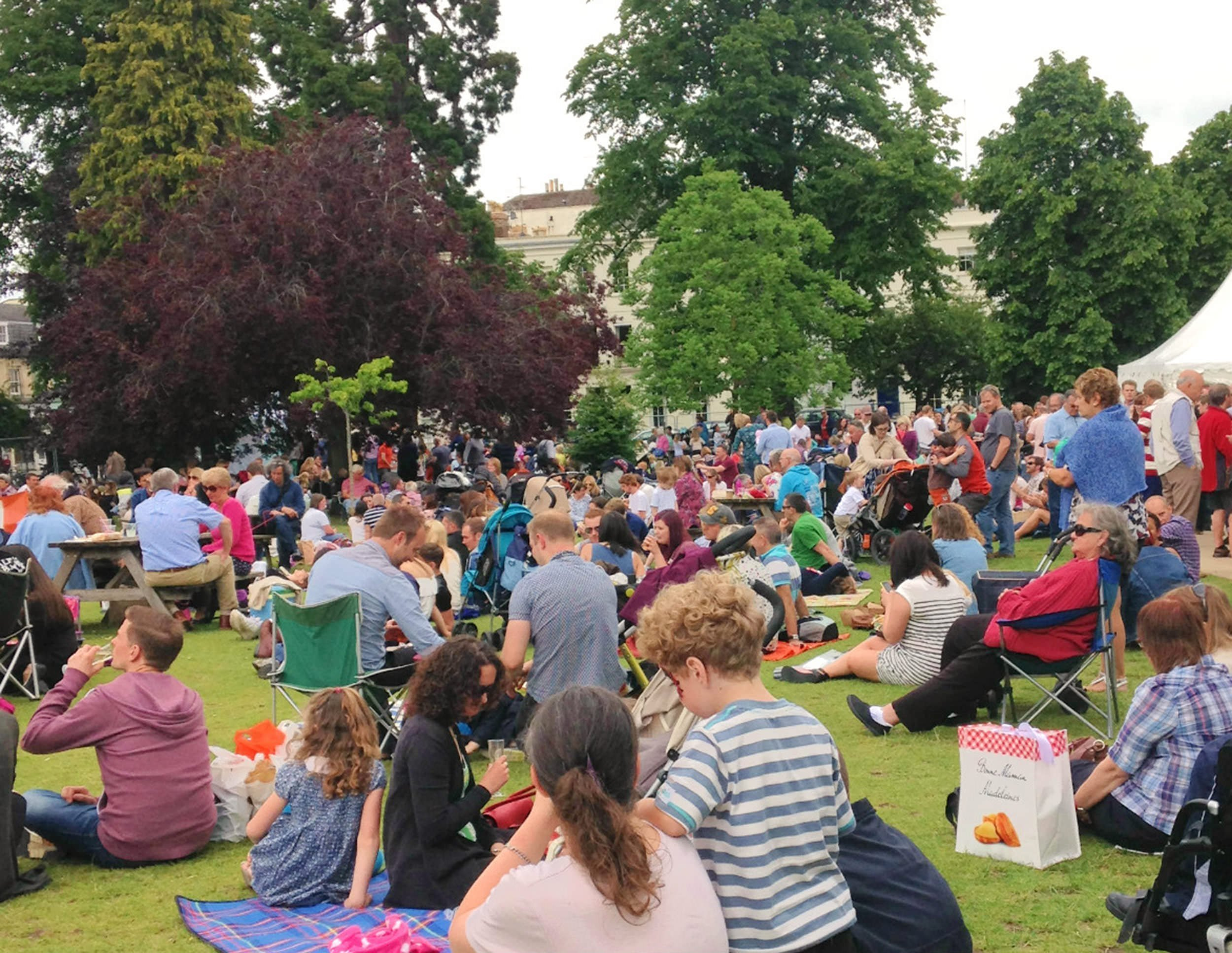 groups-of-people-sitting-on-the-grass-in-the-sun-enjoying-food-and-drink-from-the-festival