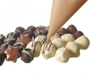 a-collection-of-truffles-being-drizzled-with-liquid-chocolate-for-decoration