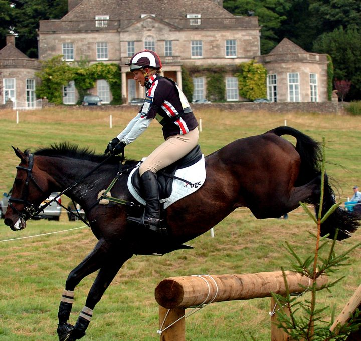 zara philips in action jumping a fence wth gatcombe house in the background