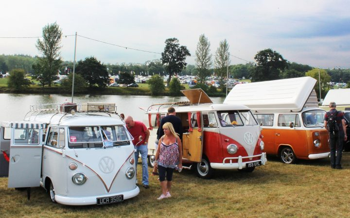 a-row-of volkswagon-campervans-against-the-back-drop-of-ragley-lakes